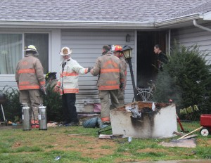 Firefighters inspect a residence on W. Crawford Avenue for damage after a doghouse caught fire Wednesday morning.